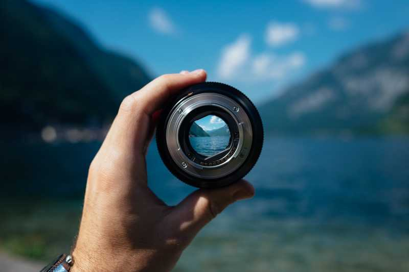Individual holding a camera lens with mountains and lake in the distance