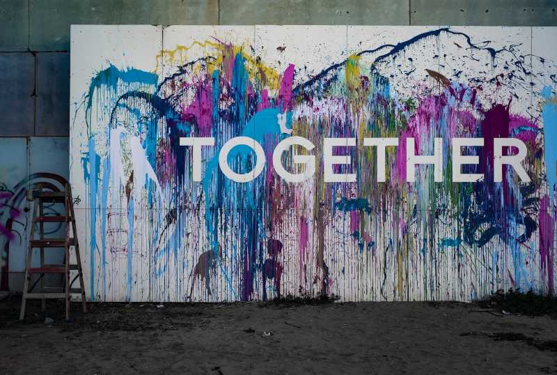 A mural of splattered multi color paint with the word Together placed above it