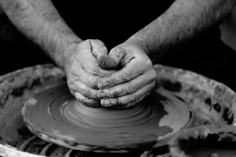 A person shaping clay by hand on a pottery wheel
