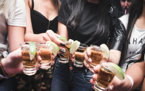 Five women standing in a circle holding shot glasses with alcohol and lime