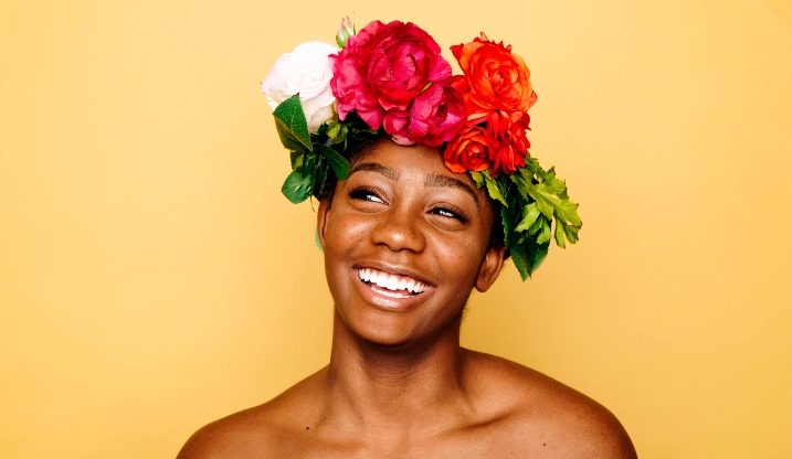 A woman smiles at the camera wearing a flower crown