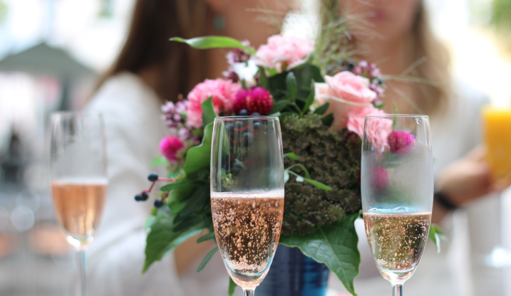 Filled champagne glasses on a table with a group of women behind