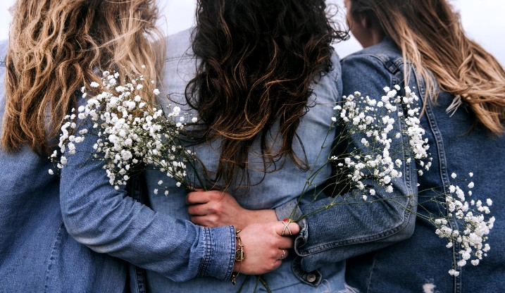 Three women on a hen party wearing denim jackets and holding white flowers