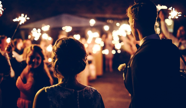 Bride and groom standing at their reception with a crowd holding sparklers