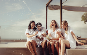 Four women sitting on a deck near a beach and opening a bottle of champagne