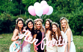 Six girls holding a hen party sign and balloons