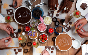 Many hands making chocolate treats on a table