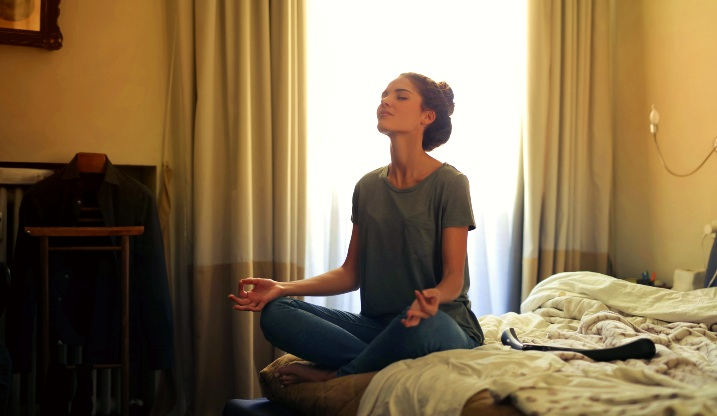 A woman sitting on her bed at home to meditate