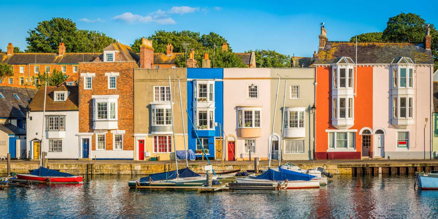 A row of pretty colourful terraced houses by a marina with boats