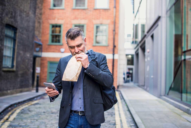 A man eating a sandwich walking down the street
