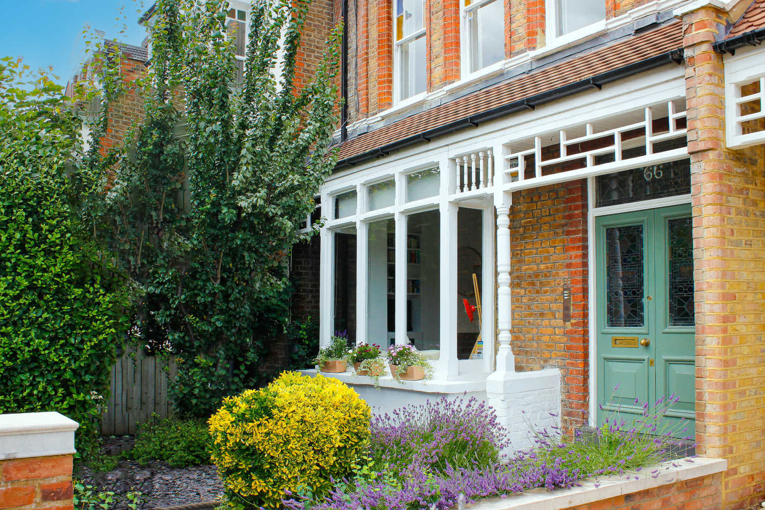 Edwardian three bedroom flat conversion home in Harringay with flowers and a green front door