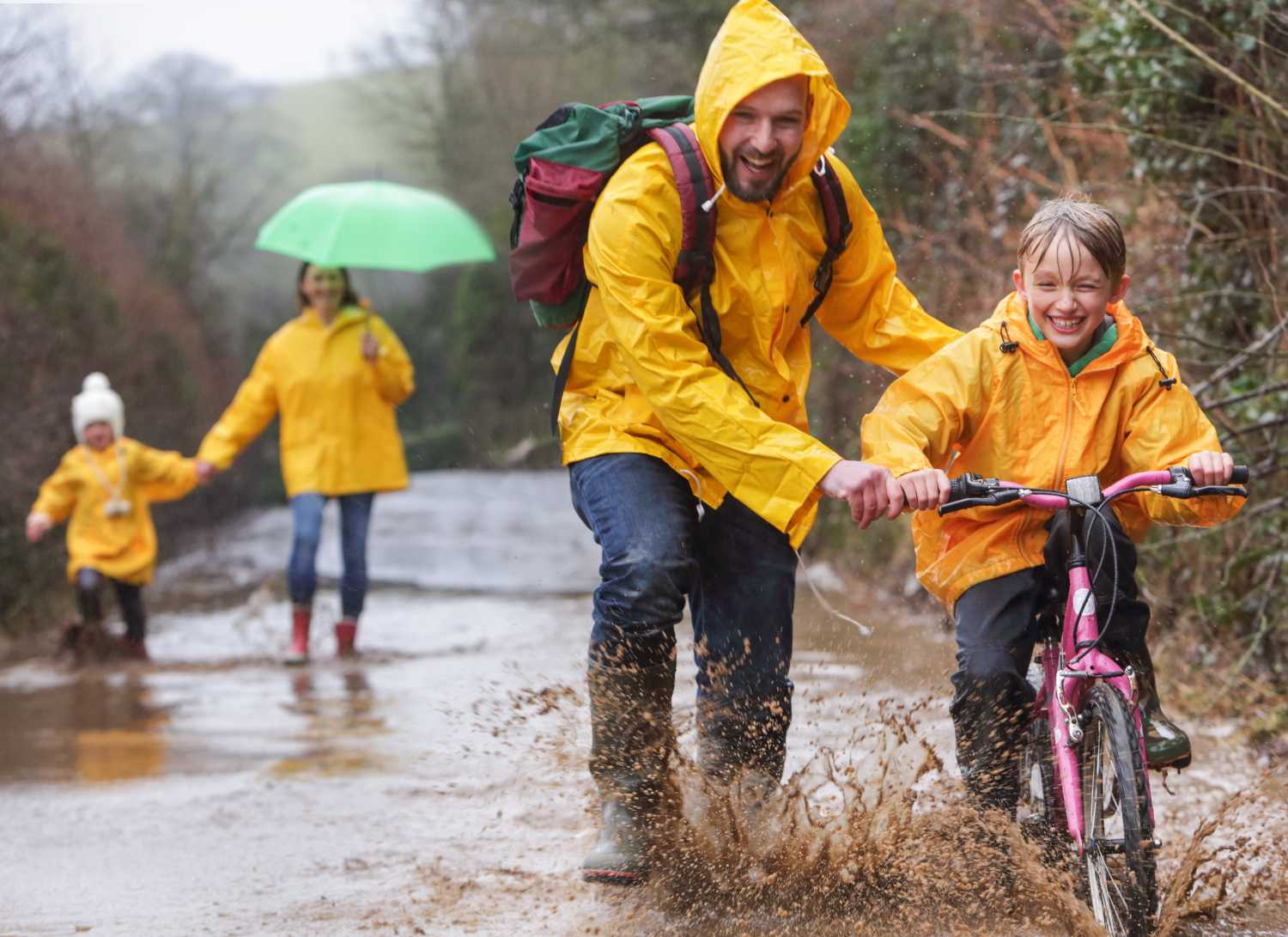 A family in yellow raincoats riding bikes and walking in the rain through a woodland