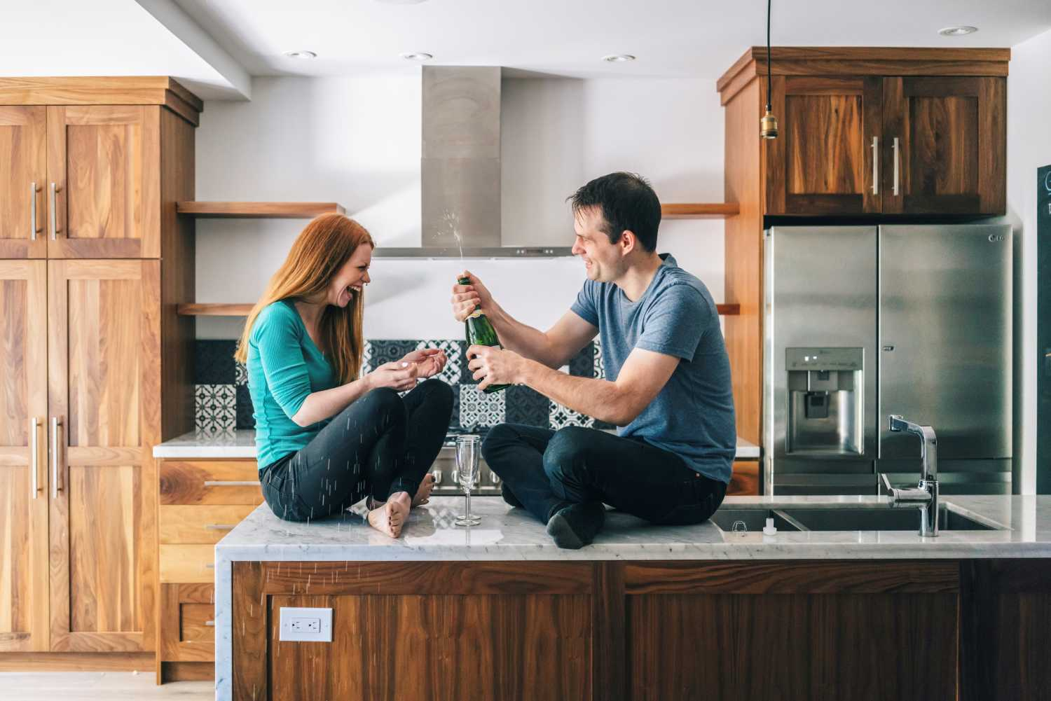A couple cracking open a bottle of champagne while sitting on kitchen worktops