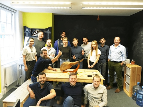 The whole YunoJuno team poses in the office with a giant iberico ham on a table in the middle of them.
