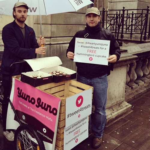 Chris and Hugo stand beside a hand cart, giving away cupcakes in the rain.