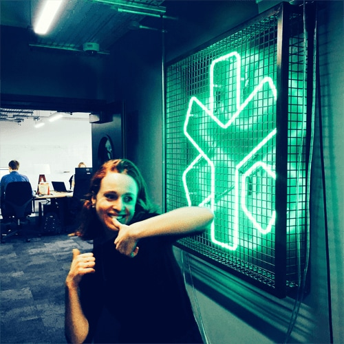 Daniela poses with two thumbs up in the hallway of the new office, next to a neon sign of the YunoJuno logo.