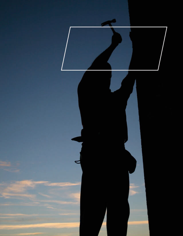 Silhouette of worker hammering on building's exterior wall