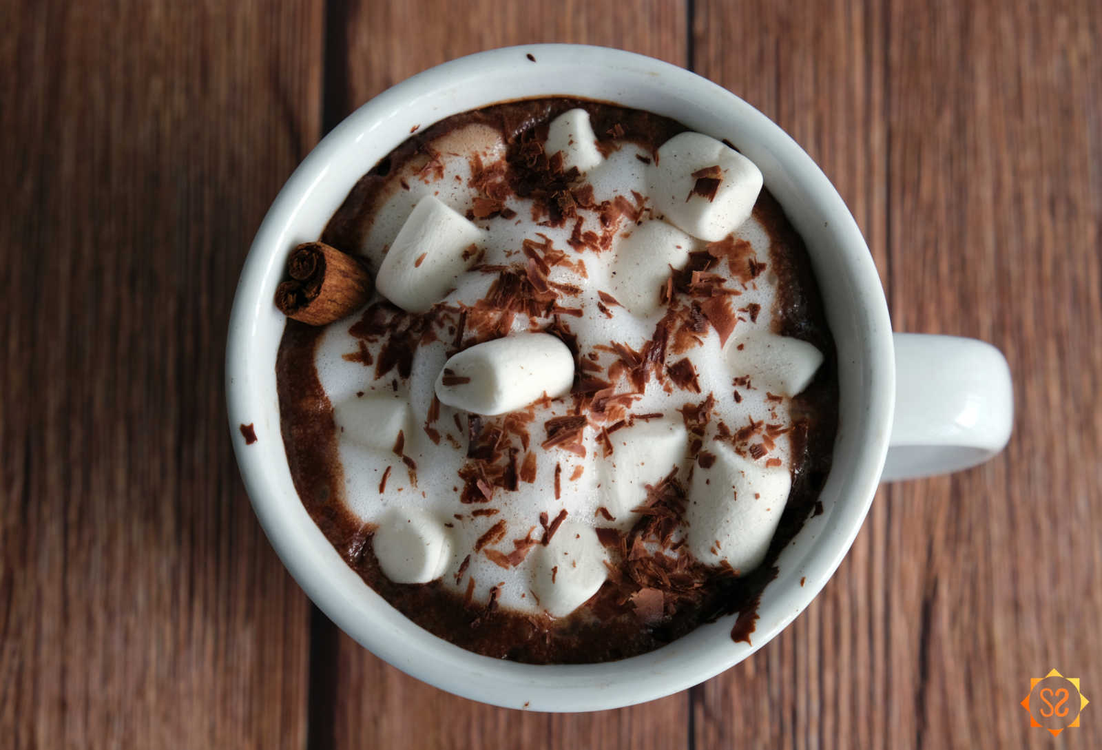 Foamy hot cacao with maca root topped with marshmallows, chocolate, and a cinnamon stick