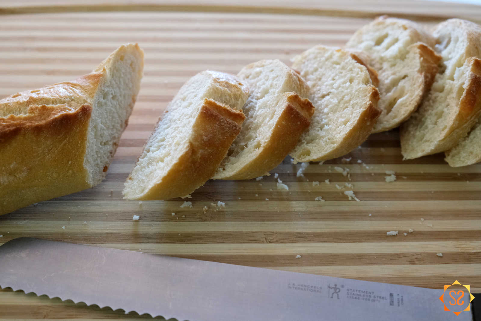 Baguette on a cutting board with several slices cut and a knife.