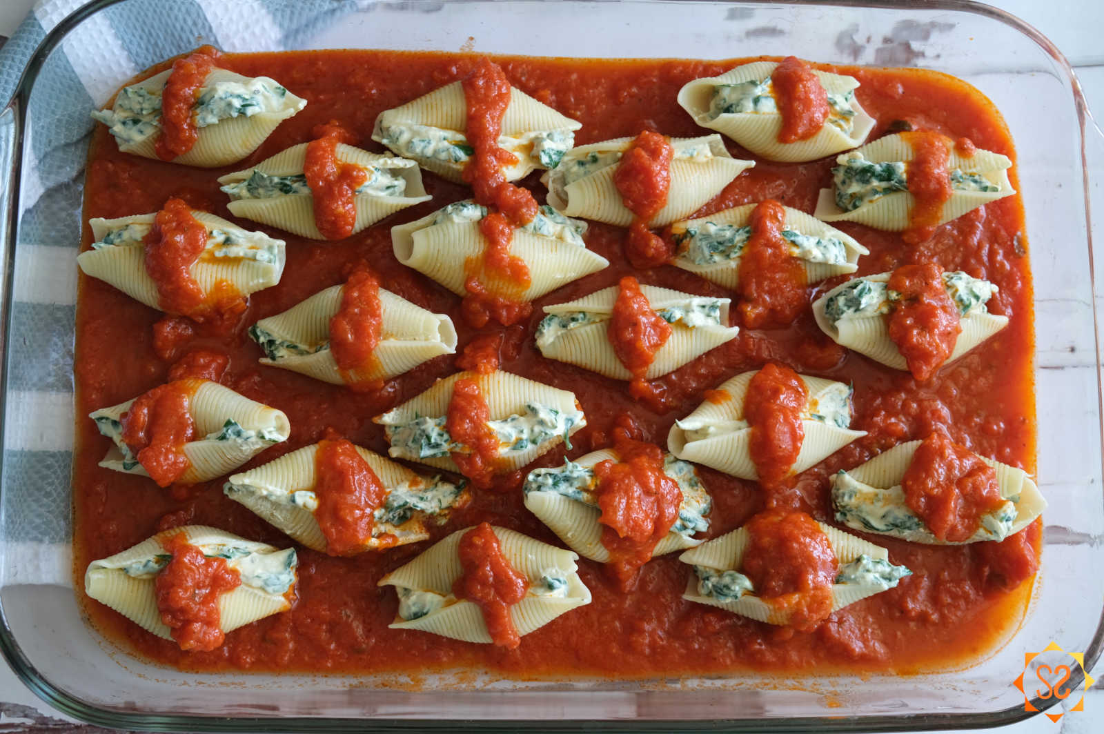 Stuffed shells in marinara sauce, in a casserole dish, ready to be baked.
