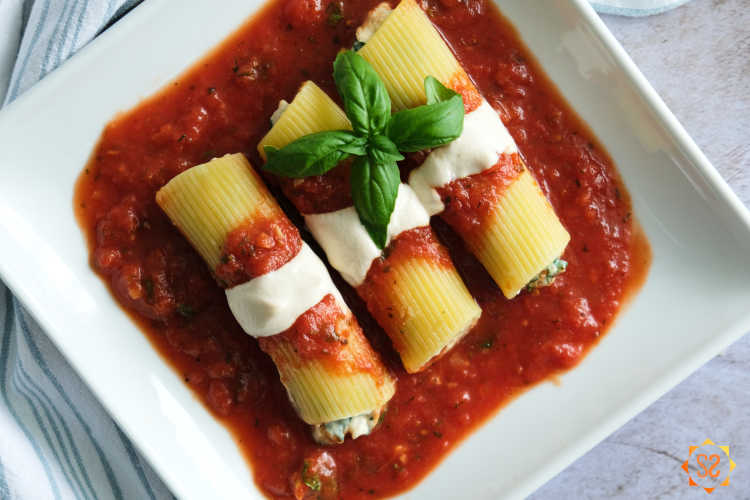 a top-down view of three vegan cannelloni on a square plate