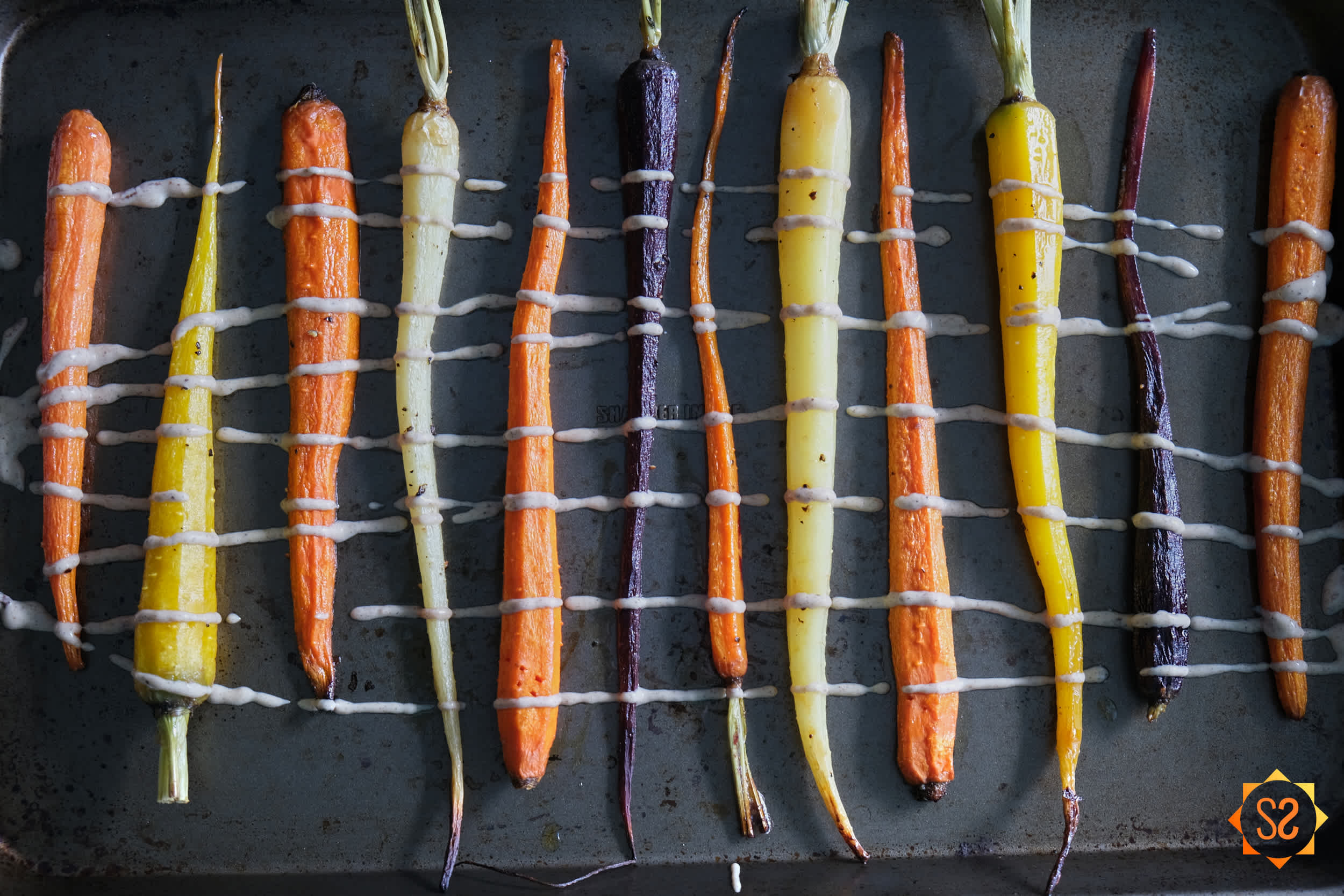 Roasted rainbow carrots on a pan with cashew-tahini sauce