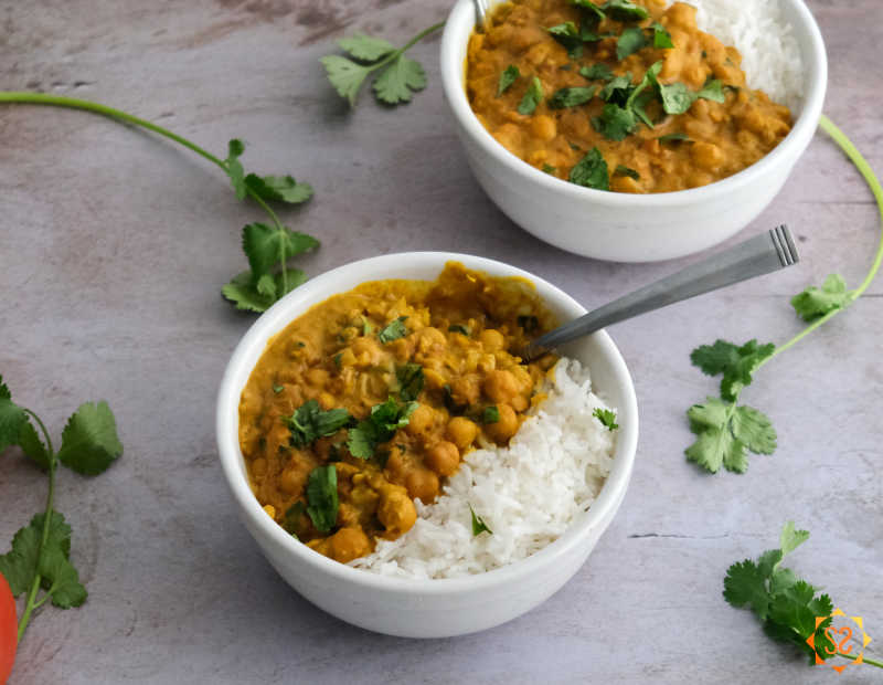 Two bowls of chickpea curry with cilantro