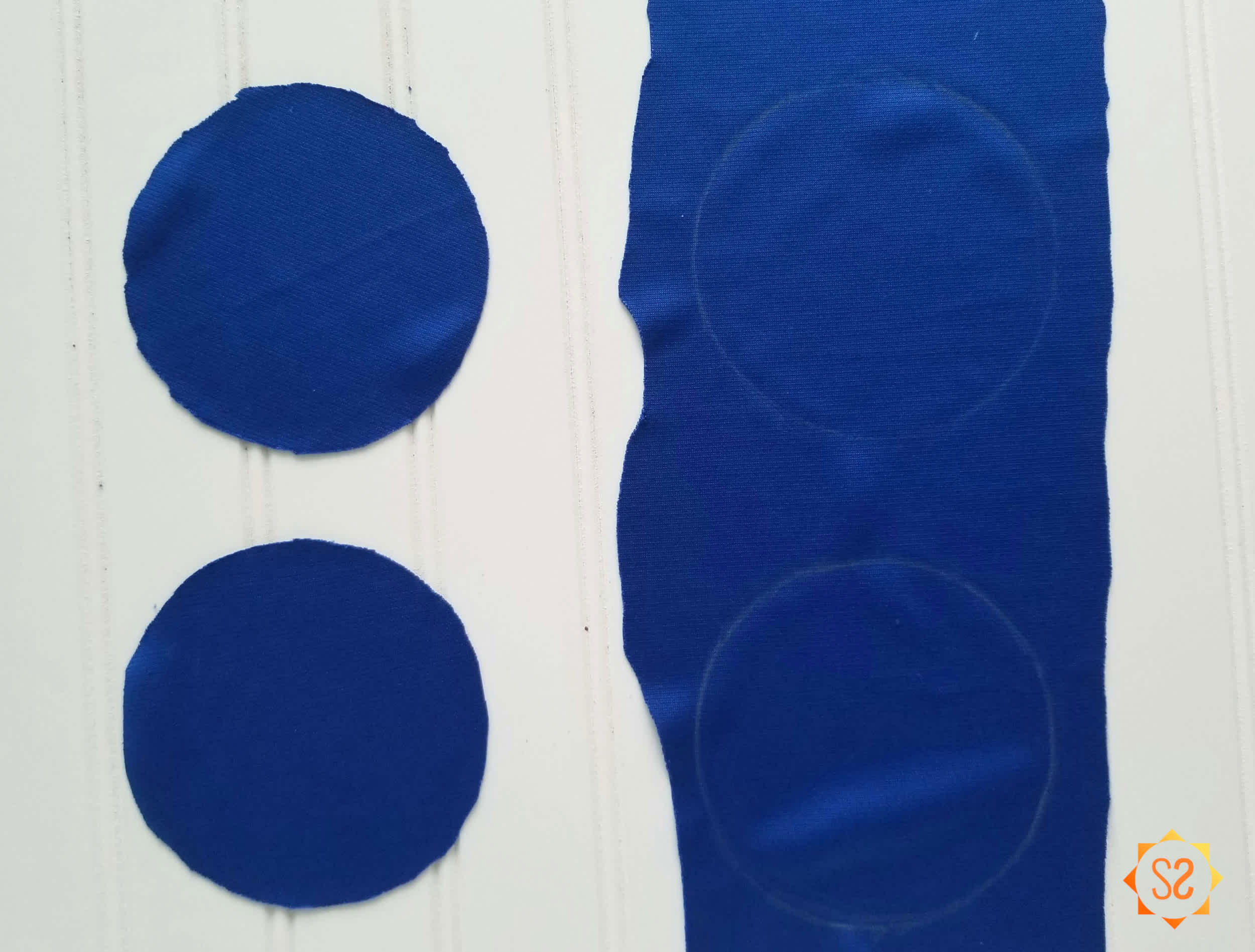 Two blue fabric circles next to a long piece of blue fabric with two circles drawn on it