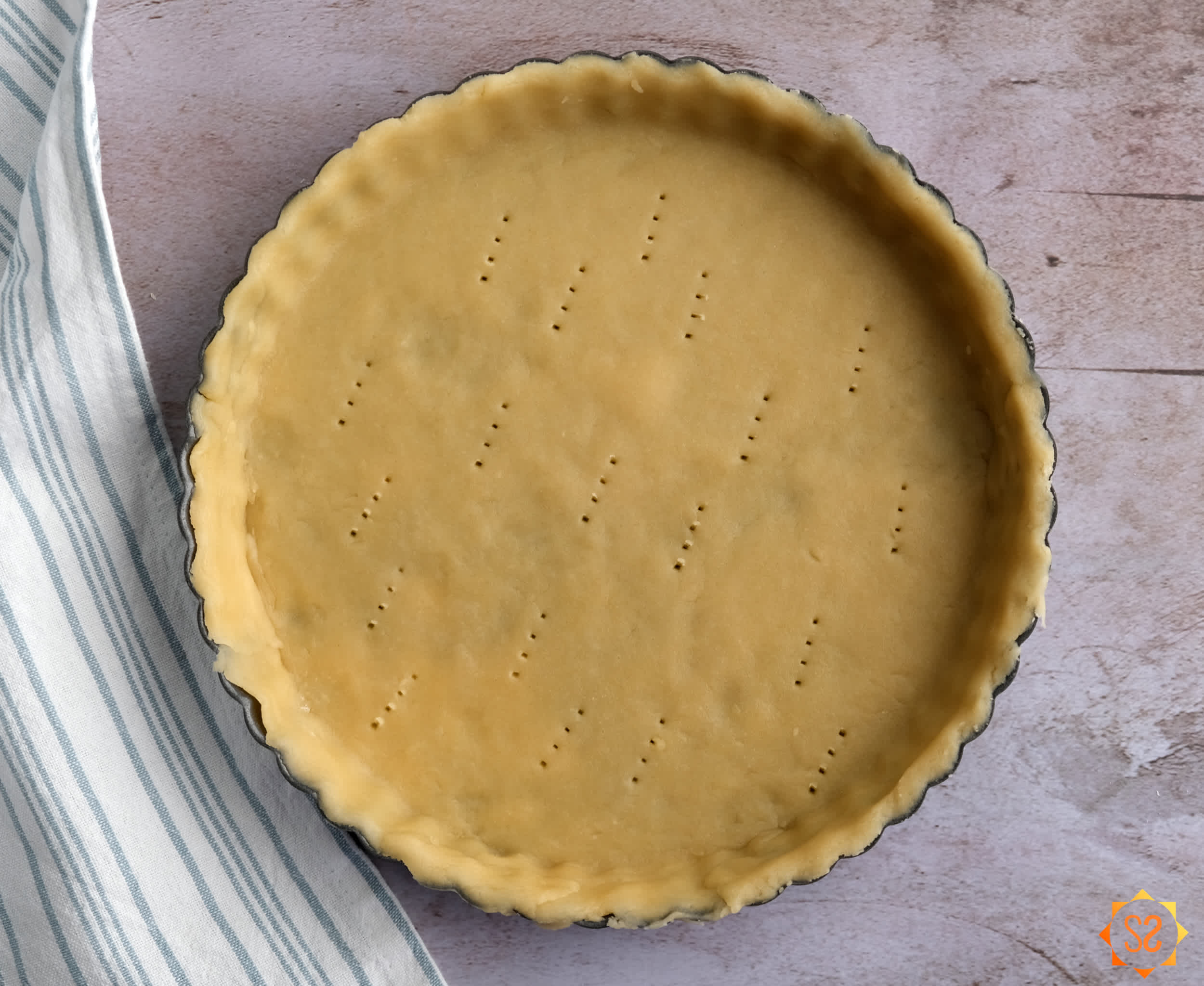 Tart crust in pan with fork holes