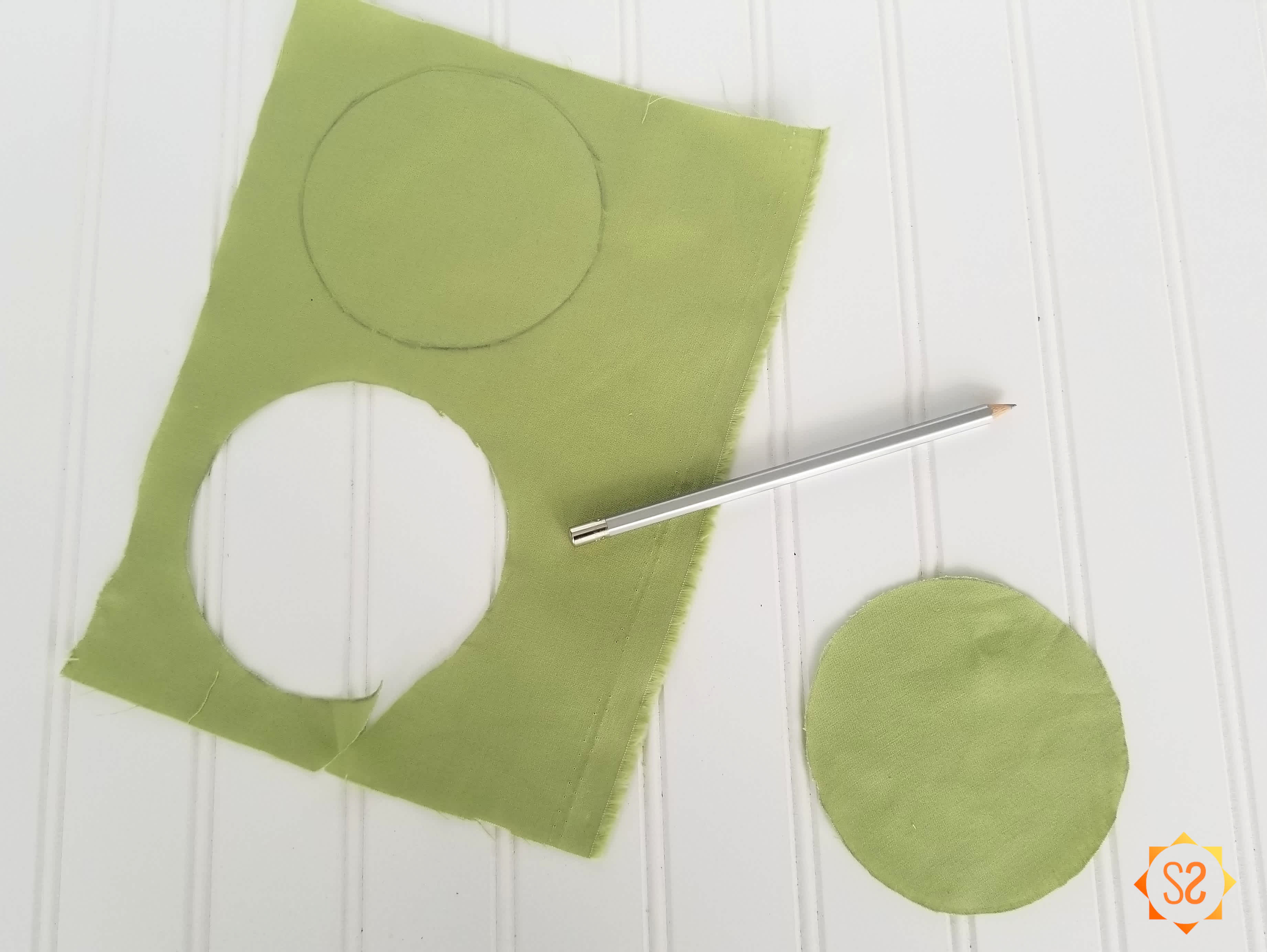 Yellow-green fabric with a circle cut out and another circle drawn on it.