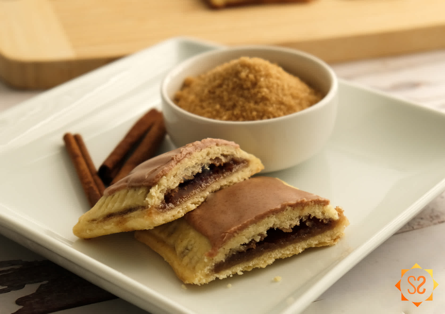 Homemade brown sugar and cinnamon Pop-tart on a plate with a dish of brown sugar and cinnamon sticks behind it