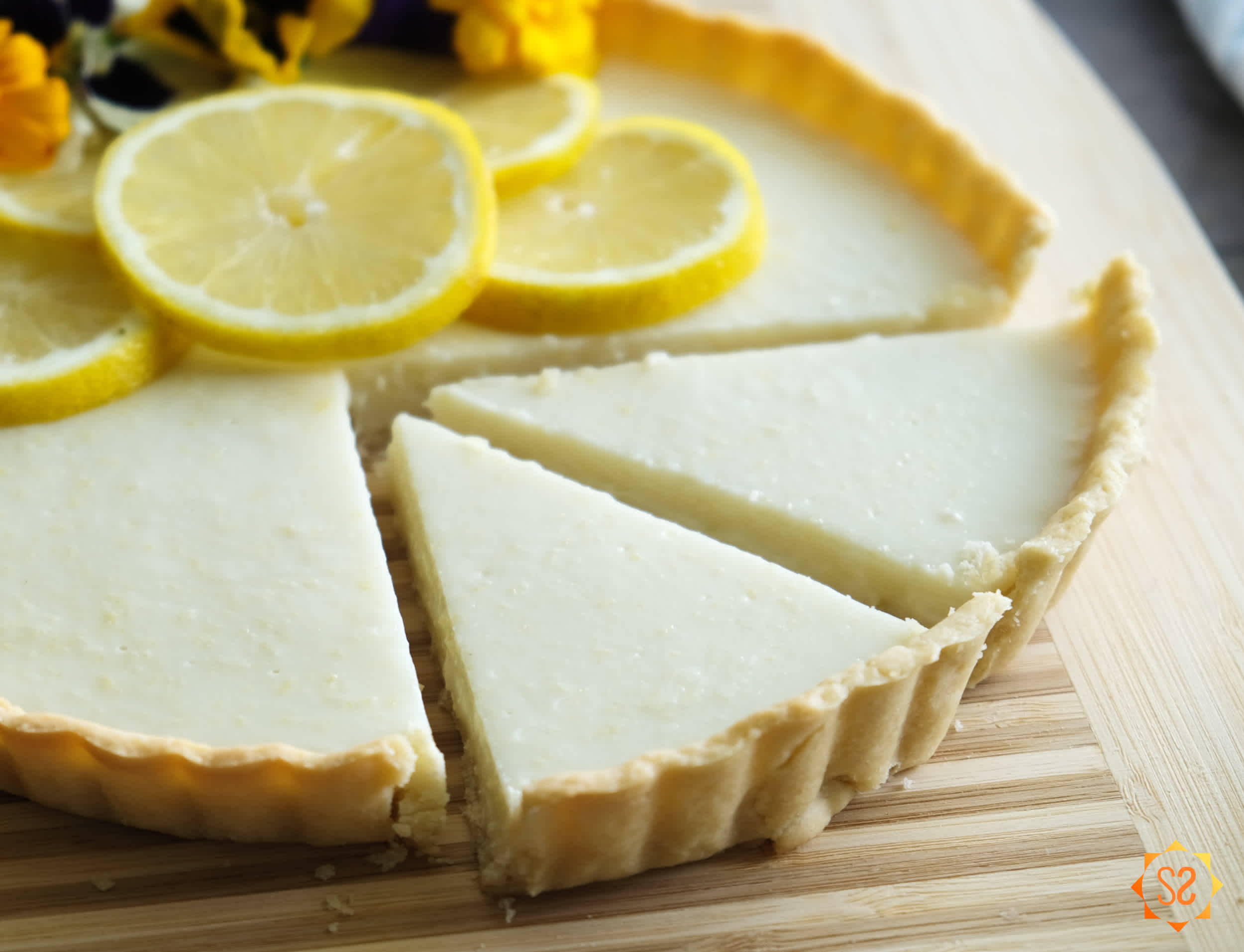 A lemon tart on a cutting board, with two slices sliced.
