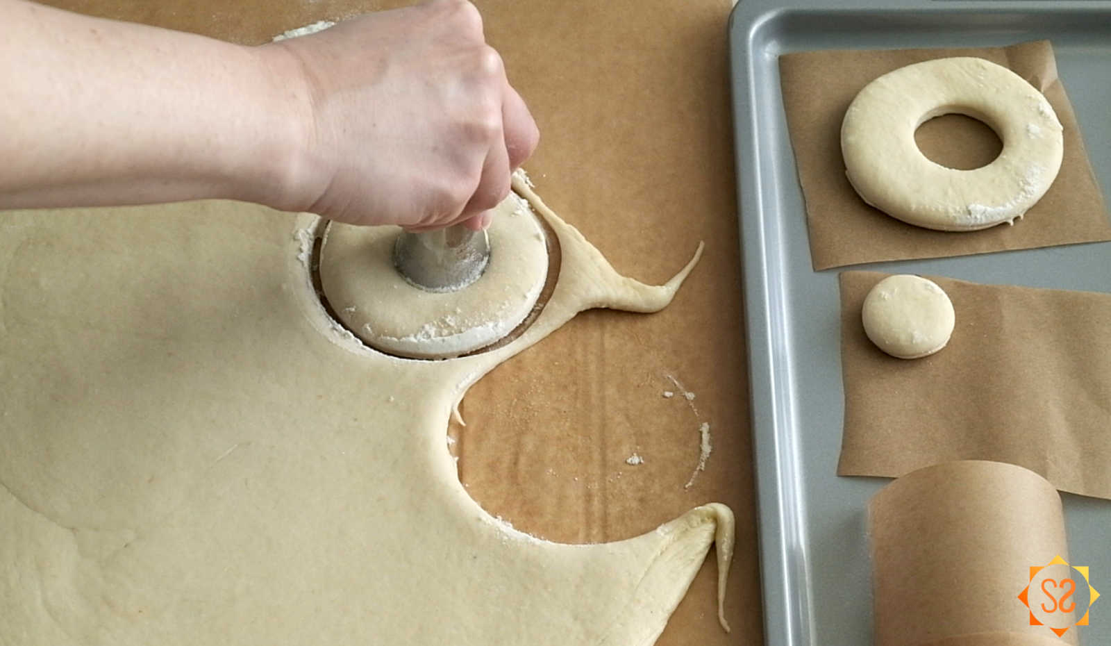 Hand cutting out a donut hole from dough, with one donut and one donut hole already cut on a baking tray on the side