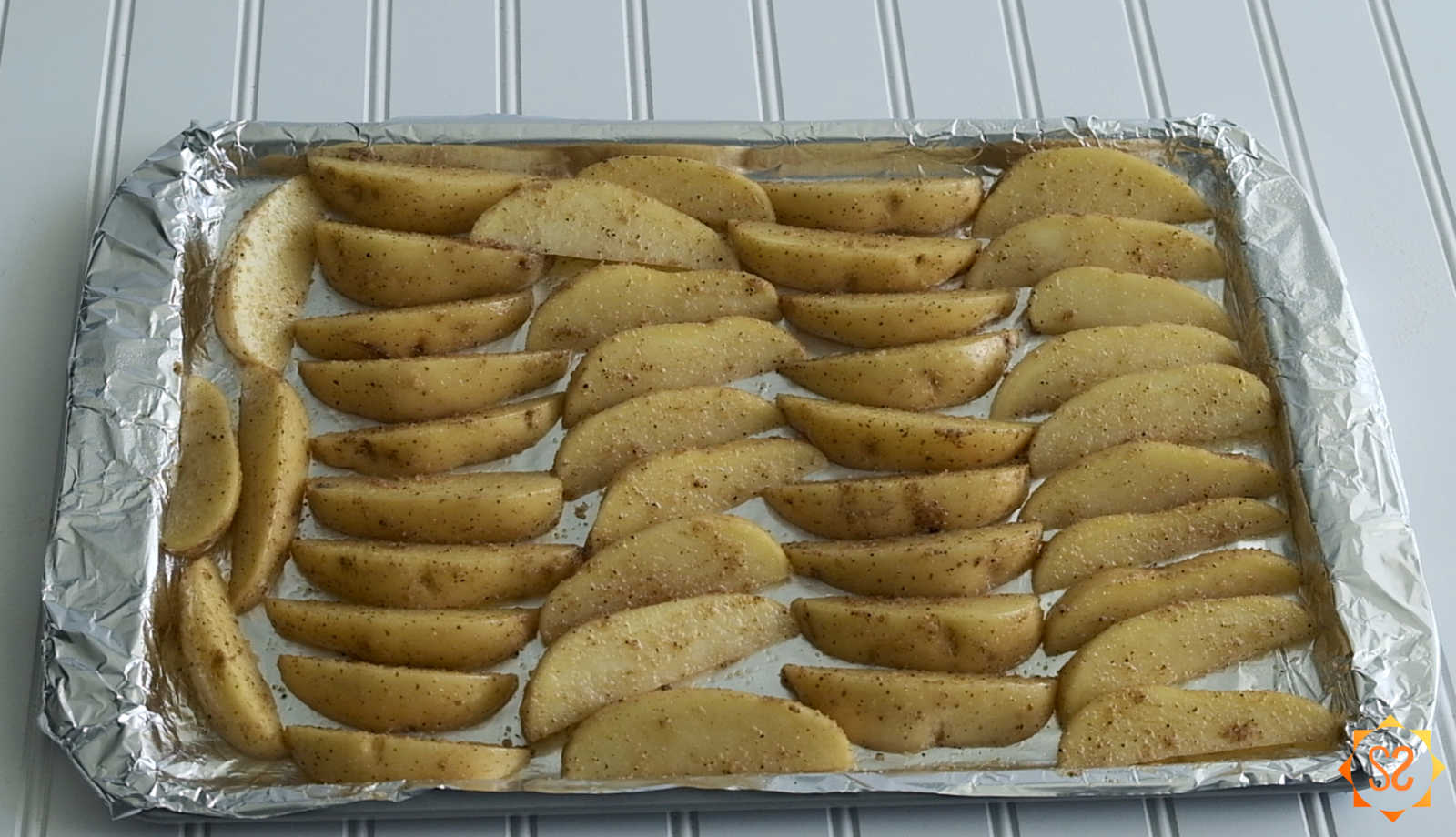 Potato wedges on a lined and oiled baking sheet