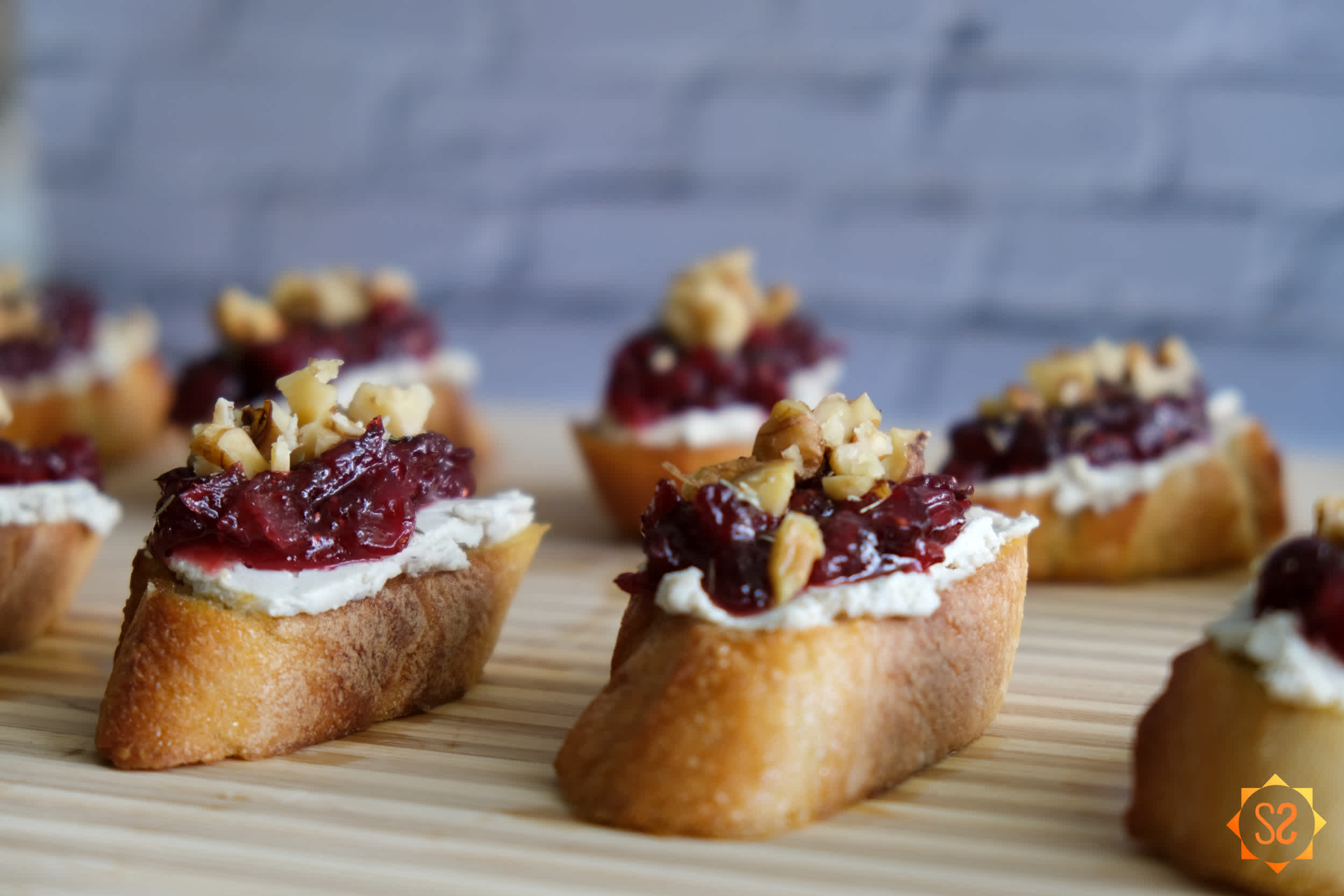 Cranberry and cashew cheese crostini on a cutting board