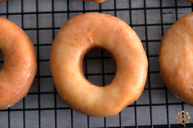 A close-up of vegan glazed donuts on a wire cooling rack