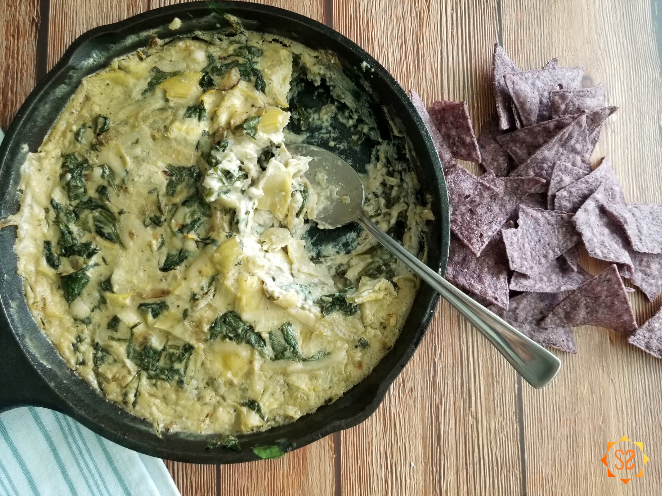 Spinach dip in a pan with a spoon, and chips on the side