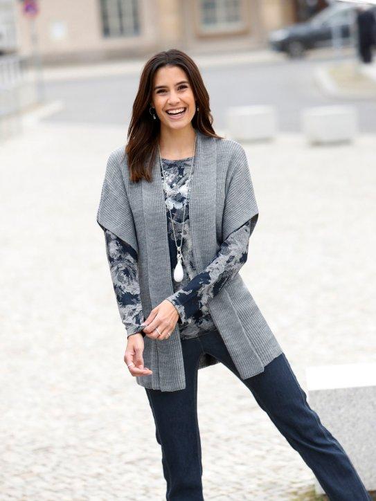 Dame in Lagenlook-Outfit aus Strickweste, Pullover und Jeans
