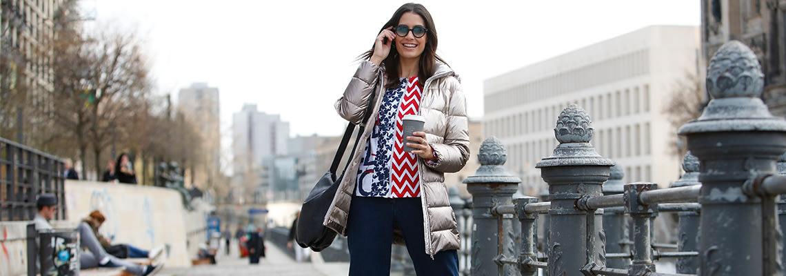 Dame in modischem Winteroutfit aus Steppjacke und Jeans