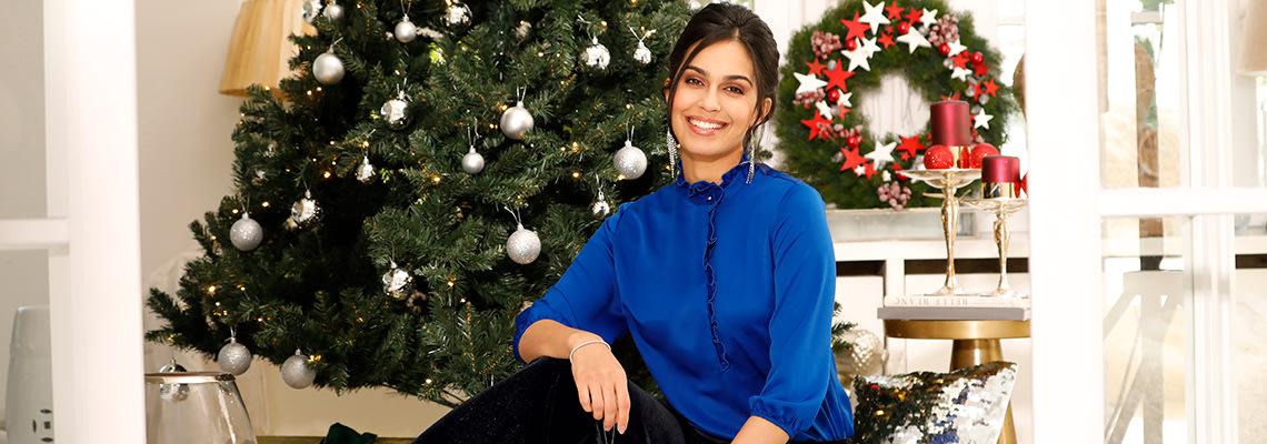 Dame in eleganter Bluse vor dem Weihnachtsbaum