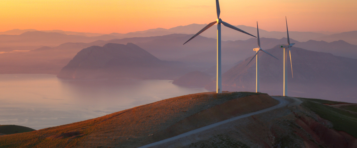Turbines situated on a hill overlooking a lake at dusk