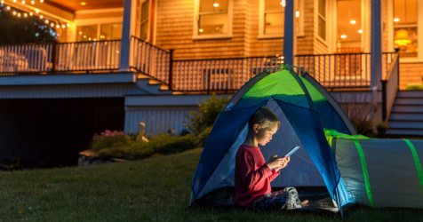 A boy in a tent in his yard on a tablet device
