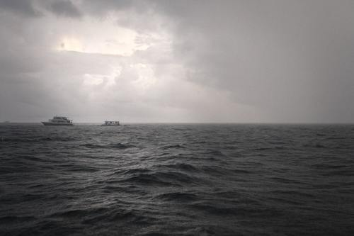 Some boats on a stormy sea.