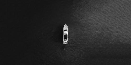 A monochrome boat in a sea.