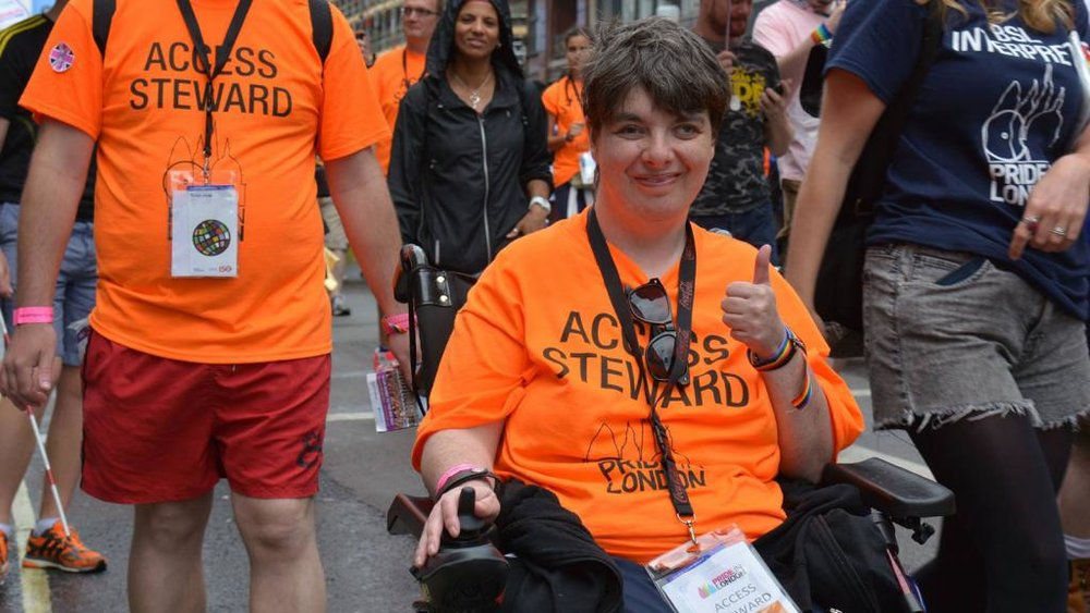 Pride steward in wheelchair giving a thumbs up