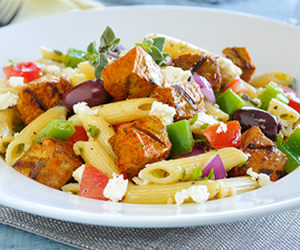 Greek salad penne in white plate on grey mat
