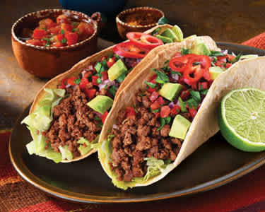 minced pork tacos on black plate with red napkin