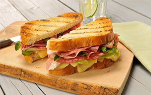 Sandwich on a wooden board made with white bread, cold cuts and cheese