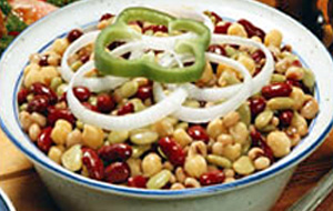 three bean salad with onions and pepper in white and blue bowl