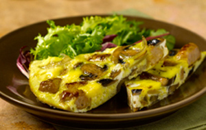slice of frittata with sausages onion and mushrooms on brown plate with salad